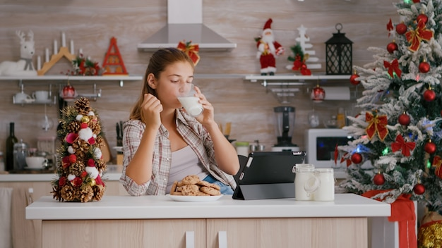 Portrait of children eating baked delicious cookies drinking milk while watching online xmas video o...