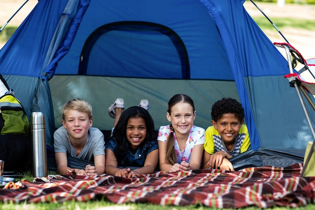 Portrait of children lying in a tent