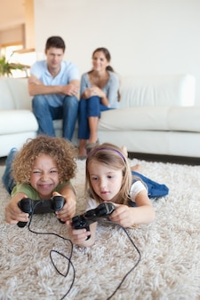 Portrait of children playing video games while their parents are watching