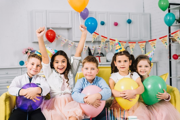 Portrait of children sitting on sofa holding balloons