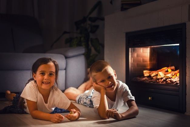 Portrait of a childs lying in front of fireplace