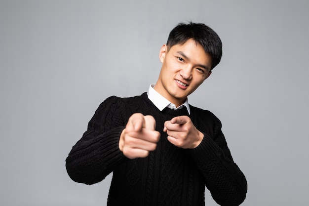 Portrait of chinese man points finger at you over isolated white wall