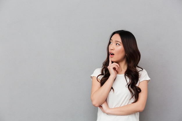 Portrait of chinese surprised woman with dark curly hair posing on camera and looking aside on copyspace with finger on lips, isolated over gray wall