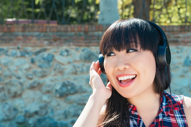 Portrait of chinese young attractive girl in urban background listening to music with headphones