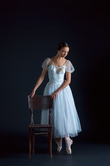 Portrait of the classical ballerina in white dress on black space
