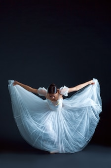 Portrait of the classical ballerina in white dress on black surface