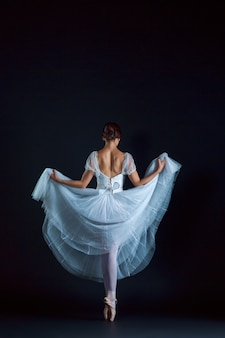 Portrait of the classical ballerina in white dress on black wall