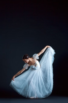 Portrait of classical ballerina in white dress on black