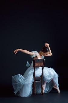 Portrait of the classical ballerina in white dress on black