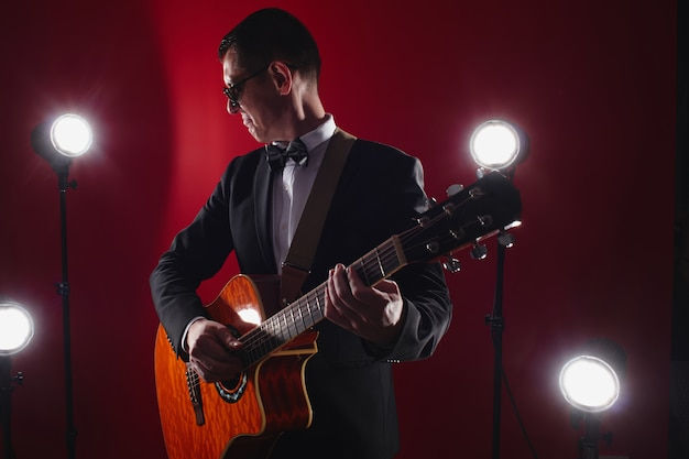 Portrait of classical musician with guitar in red studio with stage lighting. guitarist in black glasses and suit with a bow tie improvises on instrument