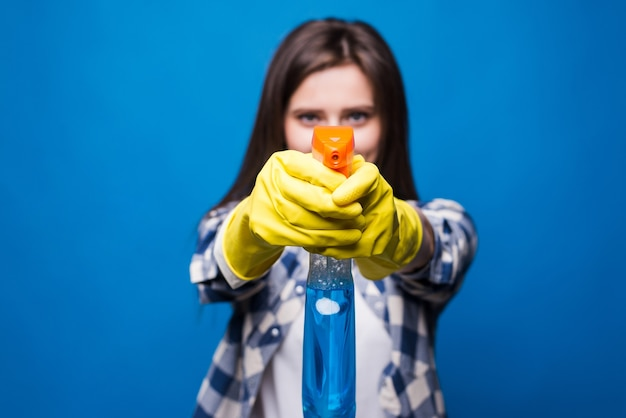 Portrait of cleaning woman aiming spray bottle in front of her isolated