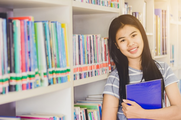 Portrait of clever asian student standing in front of book shelf iin college library