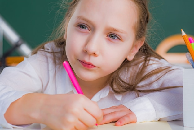 Portrait close up of kid girl drawing with pencils concept of education and reading