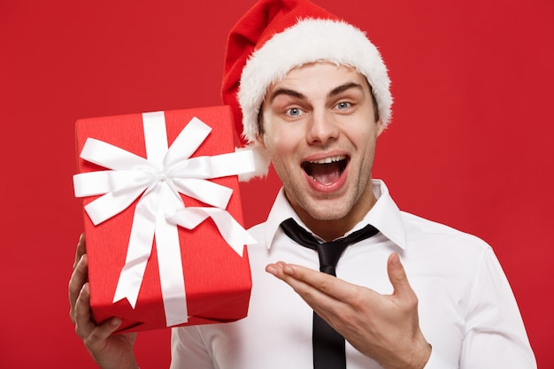Portrait close-up santa christmas businessman over red background holding red gift.