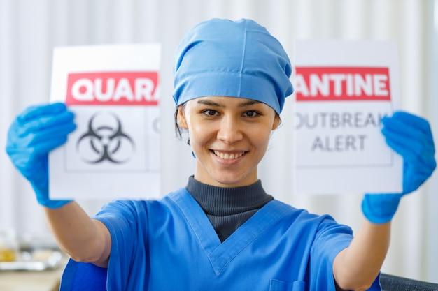 コロナウイルスのパンデミックの終わりと通常の生活とビジネスが戻ってきたときに、青い病院の制服の涙検疫発生警告紙のサインで幸せな美しい医者の肖像画のクローズアップショット。