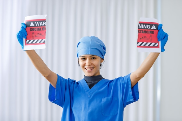 コロナウイルスのパンデミックが終わり、通常の生活とビジネスが戻ってきたときに、青い病院の制服の涙の注意検疫エリアの紙のサインで幸せな笑顔の笑う医者の肖像画のクローズアップショット。