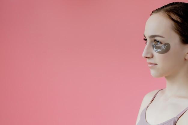 초상화는 눈 보습 패치 마스크, 스킨 케어 절차에서 웃는 젊은 여자를 닫습니다.
