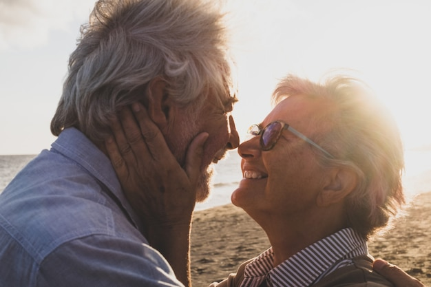 Portrait and close up of two happy in love seniors dancing smiling with the sun of the sunset between their heads