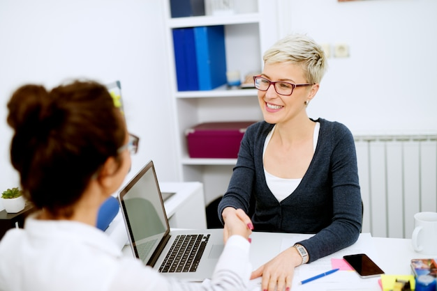Portrait close up view of middle aged beautiful short hair smiling woman sitting in front of the bank employee and shaking hands after a successful deal in the office.