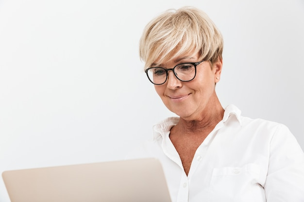 Portrait closeup of blond adult woman wearing eyeglasses smiling while using laptop computer isolated over white wall in studio