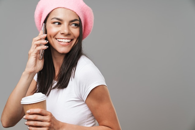 Portrait closeup of brunette pretty woman in beret smiling and talking on smartphone while drinking takeaway coffee isolated over gray wall