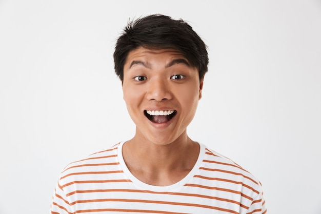 Portrait closeup of excited and happy chinese man wearing striped t-shirt smiling with perfect teeth and looking at you, isolated. concept of emotions