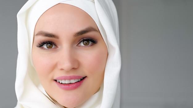 白いヒジャーブを身に着けている美しいイスラム教徒の女性の肖像画のクローズアップの顔は、カメラを見て、白い背景、コピースペースに笑みを浮かべています