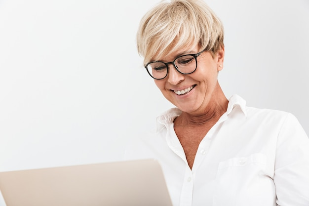 Portrait closeup of happy adult woman wearing eyeglasses smiling while using laptop computer isolated over white wall in studio