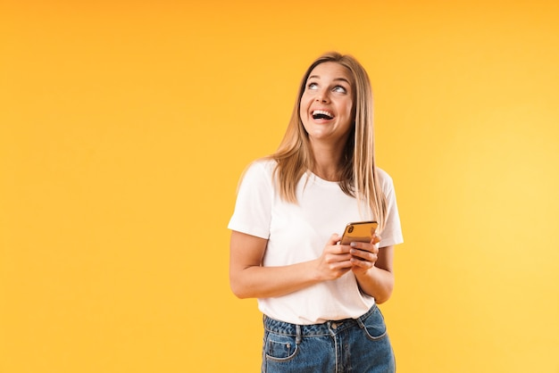 Portrait closeup of happy blond woman wearing casual t-shirt looking upward at copyspace while using smartphone isolated over yellow wall