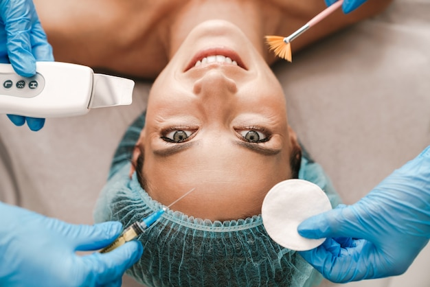 Portrait closeup of happy caucasian woman getting cosmetic procedure and injection while lying in beauty salon