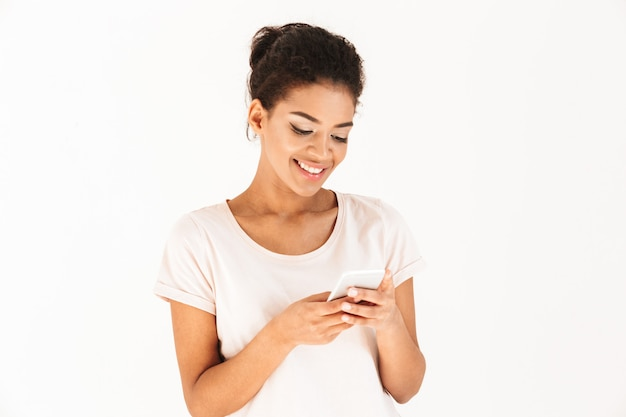 Portrait closeup of mixed race woman in casual posing with mobile phone in hands, isolated over white wall