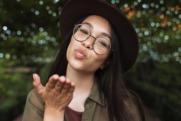夜の公園を歩きながらエアキスを送信帽子と眼鏡を身に着けている美しい女性の肖像画のクローズアップ