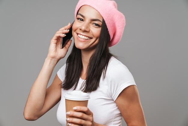 灰色の壁に隔離された持ち帰り用コーヒーを飲みながら笑顔とスマートフォンで話しているベレー帽の陽気なきれいな女性の肖像画のクローズアップ