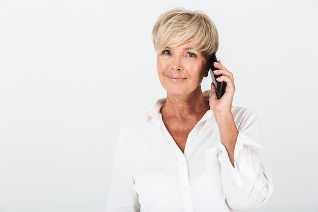 スタジオの白い壁の上に分離された携帯電話で笑顔と話をしている短いブロンドの髪を持つ自信を持って大人の女性の肖像画のクローズアップ