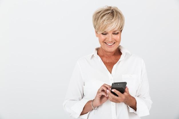 スタジオで白い壁の上に分離された携帯電話を笑顔と保持している短いブロンドの髪を持つエレガントな大人の女性の肖像画のクローズアップ