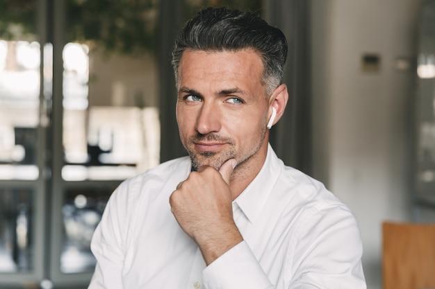 흰색 이어 버드를 사용하여 사무실에서 작업하는 동안 옆으로보고 턱을 만지고 흰색 셔츠를 입고 유럽 잘 생긴 남자 30 대의 초상화 근접 촬영