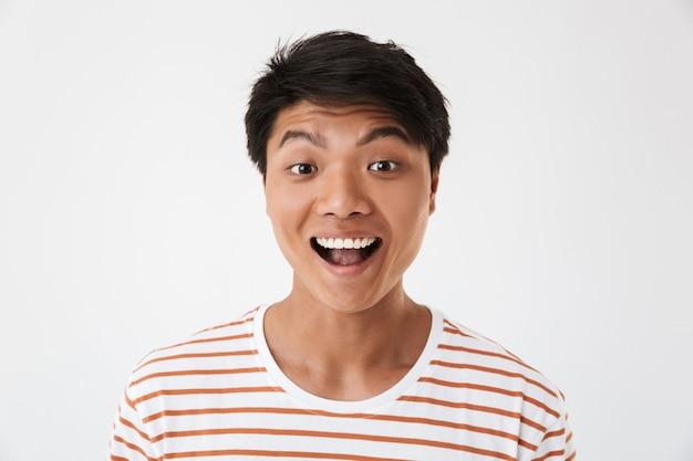 完璧な歯で笑って、孤立した、あなたを見ている縞模様のtシャツを着て興奮して幸せな中国人男性の肖像画のクローズアップ。感情の概念