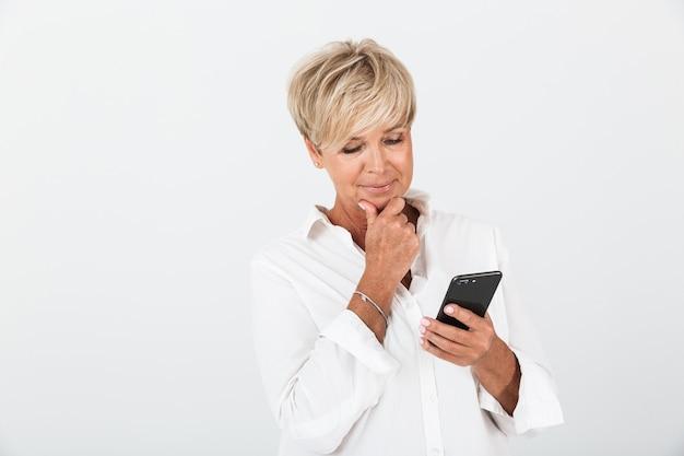 スタジオで白い壁に隔離された携帯電話を考えて保持している短いブロンドの髪を持つゴージャスな大人の女性の肖像画のクローズアップ