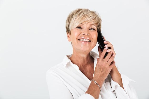 スタジオで白い壁に隔離された携帯電話で笑顔と話をして短いブロンドの髪を持つ幸せな大人の女性の肖像画のクローズアップ