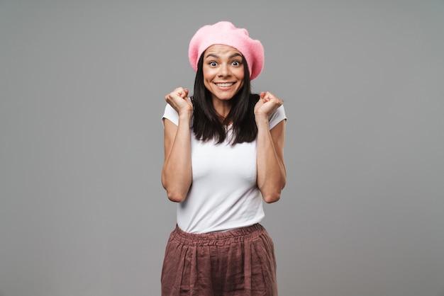 Портрет крупным планом счастливой красивой женщины в простой футболке и берете, радуясь и сжимая кулаки, изолированные на серой стене