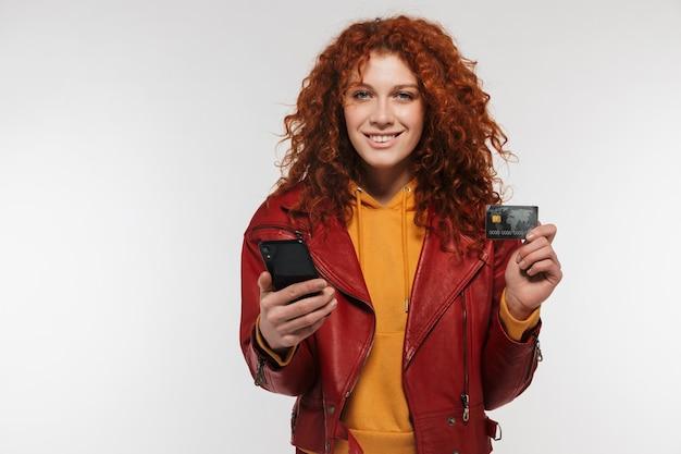 Портрет крупным планом счастливой рыжей женщины 20-х годов в кожаной куртке, держащей мобильный телефон и пластиковую кредитную карту, изолированную над белой стеной