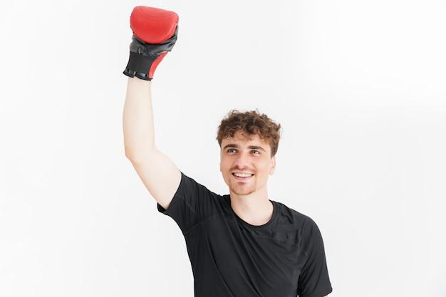勝利を祝い、白い壁に隔離されたボクシンググローブで腕を上げるtシャツのうれしそうな男の肖像画のクローズアップ