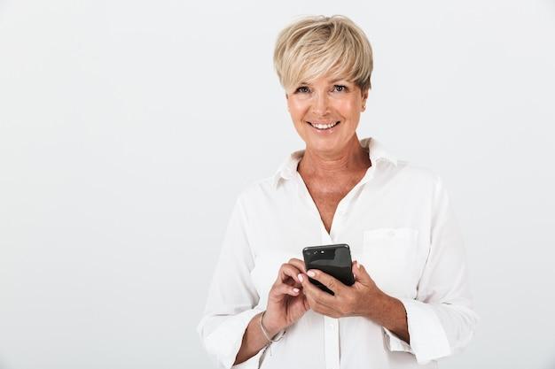 スタジオで白い壁の上に分離された携帯電話を笑顔と保持している短いブロンドの髪を持つ楽しい大人の女性の肖像画のクローズアップ