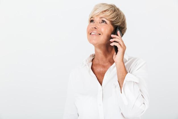 スタジオの白い壁の上に分離された携帯電話で微笑んで話している短いブロンドの髪を持つ楽しい大人の女性の肖像画のクローズアップ