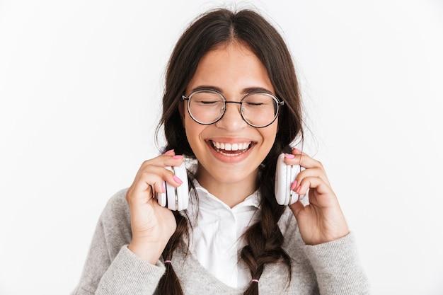 白い壁に隔離されたヘッドフォンで音楽を聴きながら笑っている眼鏡をかけている楽しい10代の少女の肖像画のクローズアップ