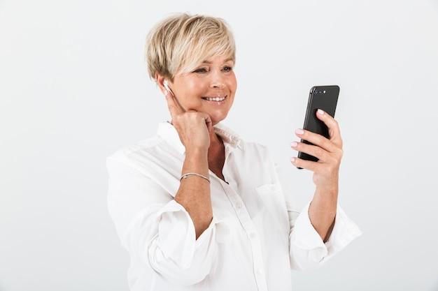 スタジオで白い壁の上に分離された携帯電話とイヤポッドを使用して短いブロンドの髪を持つ中年の大人の女性の肖像画のクローズアップ