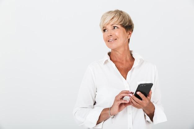 スタジオで白い壁の上に分離された携帯電話を笑顔と保持している短いブロンドの髪を持つ楽観的な大人の女性の肖像画のクローズアップ