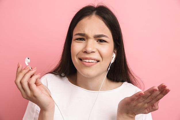 ピンクの壁に隔離されたイヤホンを着用して保持しながら眉をひそめている困惑した少女の肖像画のクローズアップ