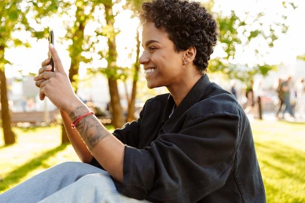 都市公園のベンチに座っている間スマートフォンでselfieportraitを取っている巻き毛を持つ満足している女性の肖像画のクローズアップ