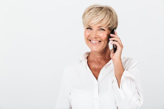 スタジオで白い壁に隔離された携帯電話で笑顔と話をしている短いブロンドの髪を持つポジティブな大人の女性の肖像画のクローズアップ